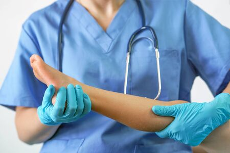 Mano del medico che tiene la gamba del paziente, esame dei pazienti in ospedale. Chirurgo, chirurgo, anestesista che tiene la gamba del paziente. Chirurgia ER professionale, concetto di assistenza sanitaria.