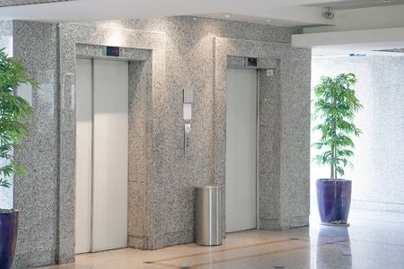 View of two elevator doors in office building. Wide angle view of several modern elevators with closed doors. Elevators in the modern lobby.