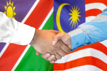 Business handshake on the background of two flags. Men handshake on the background of the Namibia and Malaysia flag. Support concept