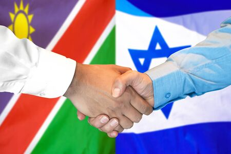 Business handshake on the background of two flags. Men handshake on the background of the Namibia and Israel flag. Support concept