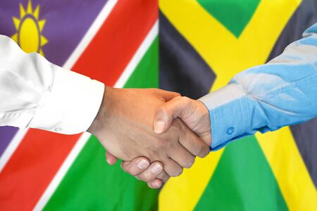 Business handshake on the background of two flags. Men handshake on the background of the Namibia and Jamaica flag. Support concept Zdjęcie Seryjne