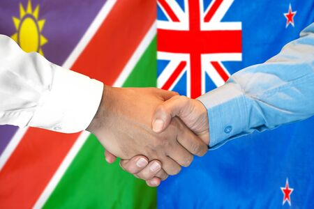 Business handshake on the background of two flags. Men handshake on the background of the Namibia and New Zealand flag. Support concept