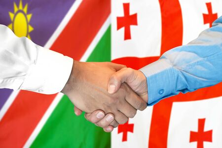 Business handshake on the background of two flags. Men handshake on the background of the Namibia and Georgia flag. Support concept Zdjęcie Seryjne