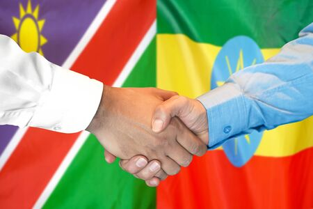 Business handshake on the background of two flags. Men handshake on the background of the Namibia and Ethiopia flag. Support concept