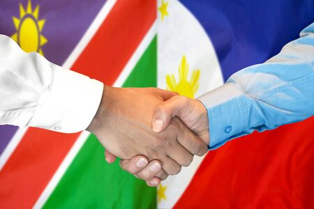 Business handshake on the background of two flags. Men handshake on the background of the Namibia and Philippines flag. Support concept