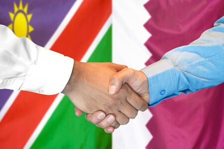 Business handshake on the background of two flags. Men handshake on the background of the Namibia and Qatar flag. Support concept