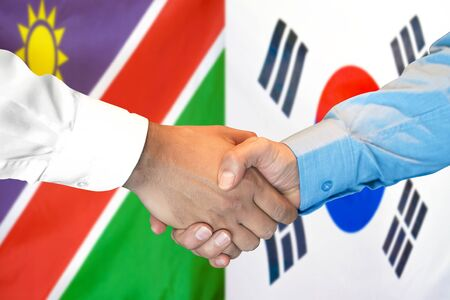 Business handshake on the background of two flags. Men handshake on the background of the Namibia and South Korea flag. Support concept