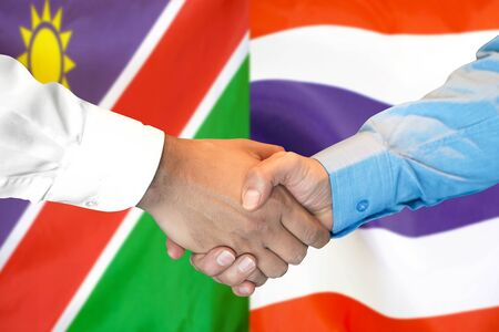 Business handshake on the background of two flags. Men handshake on the background of the Namibia and Thailand flag. Support concept