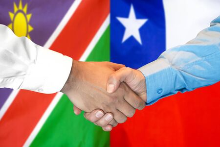 Business handshake on the background of two flags. Men handshake on the background of the Namibia and Chile flag. Support concept Zdjęcie Seryjne