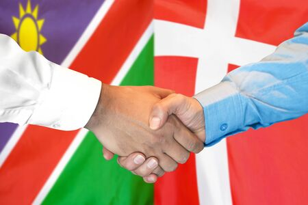 Business handshake on the background of two flags. Men handshake on the background of the Namibia and Denmark flag. Support concept