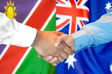 Business handshake on the background of two flags. Men handshake on the background of the Namibia and Australia flag. Support concept