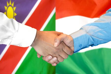 Business handshake on the background of two flags. Men handshake on the background of the Namibia and Hungary flag. Support concept Zdjęcie Seryjne