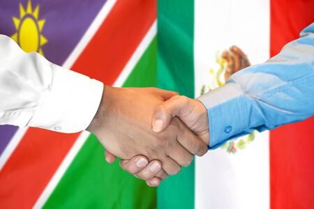 Business handshake on the background of two flags. Men handshake on the background of the Namibia and Mexico flag. Support concept