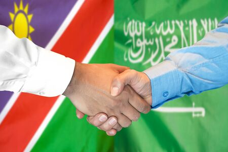 Business handshake on the background of two flags. Men handshake on the background of the Namibia and Saudi Arabia flag. Support concept Zdjęcie Seryjne