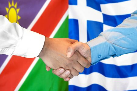 Business handshake on the background of two flags. Men handshake on the background of the Namibia and Greece flag. Support concept