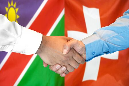 Business handshake on the background of two flags. Men handshake on the background of the Namibia and Switzerland flag. Support concept