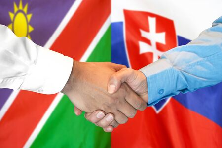 Business handshake on the background of two flags. Men handshake on the background of the Namibia and Slovakia flag. Support concept
