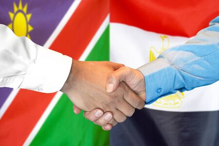 Business handshake on the background of two flags. Men handshake on the background of the Namibia and Egypt flag. Support concept