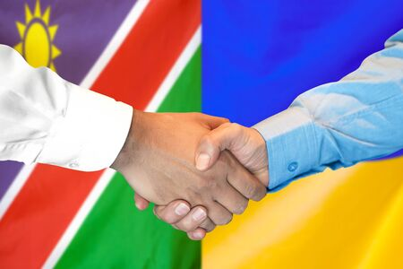 Business handshake on the background of two flags. Men handshake on the background of the Namibia and Ukraine flag. Support concept Zdjęcie Seryjne
