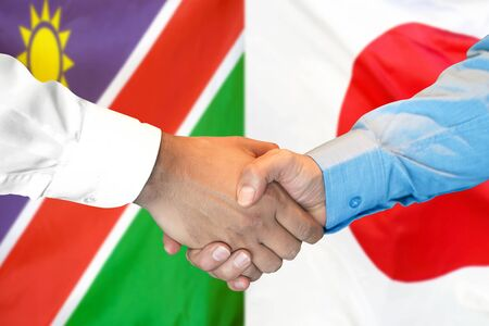 Business handshake on the background of two flags. Men handshake on the background of the Namibia and Japan flag. Support concept Zdjęcie Seryjne