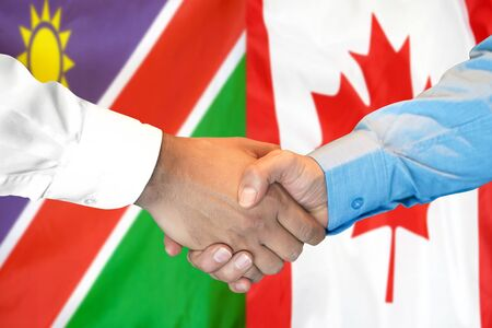 Business handshake on the background of two flags. Men handshake on the background of the Namibia and Canada flag. Support concept Zdjęcie Seryjne