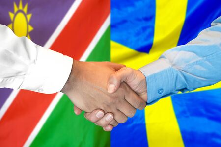 Business handshake on the background of two flags. Men handshake on the background of the Namibia and Sweden flag. Support concept