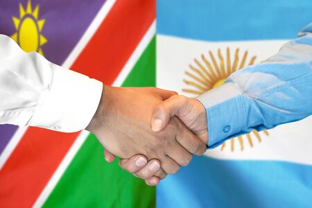 Business handshake on the background of two flags. Men handshake on the background of the Namibia and Argentina flag. Support concept
