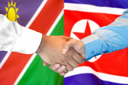 Business handshake on the background of two flags. Men handshake on the background of the Namibia and North Korea flag. Support concept
