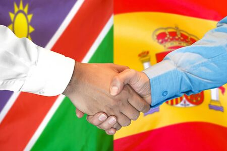 Business handshake on the background of two flags. Men handshake on the background of the Namibia and Spain flag. Support concept Zdjęcie Seryjne