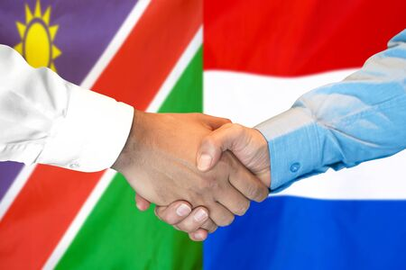 Business handshake on the background of two flags. Men handshake on the background of the Namibia and Netherlands flag. Support concept Zdjęcie Seryjne