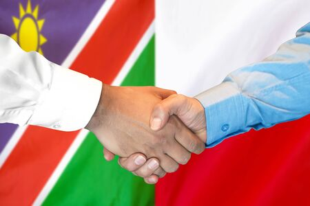 Business handshake on the background of two flags. Men handshake on the background of the Namibia and Poland flag. Support concept