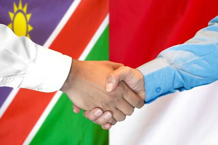 Business handshake on the background of two flags. Men handshake on the background of the Namibia and Monaco flag. Support concept