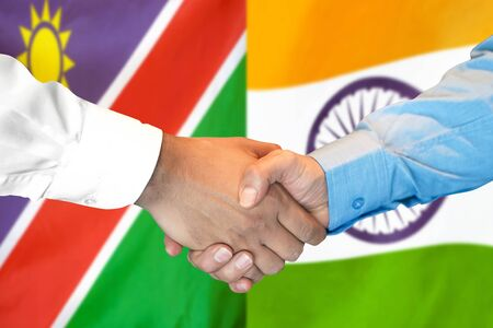 Business handshake on the background of two flags. Men handshake on the background of the Namibia and India flag. Support concept Zdjęcie Seryjne