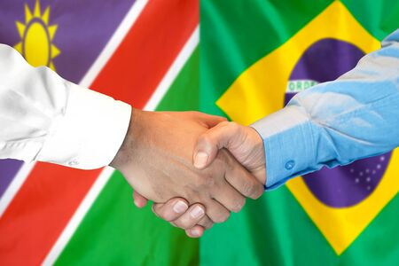 Business handshake on the background of two flags. Men handshake on the background of the Namibia and Brazil flag. Support concept