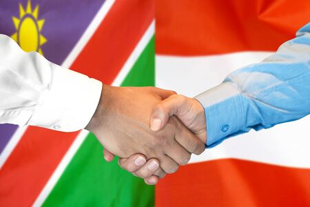 Business handshake on the background of two flags. Men handshake on the background of the Namibia and Austria flag. Support concept