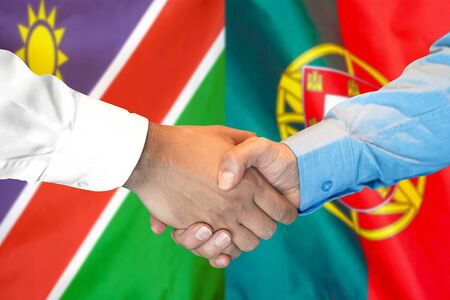 Business handshake on the background of two flags. Men handshake on the background of the Namibia and Portugal flag. Support concept