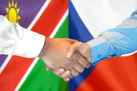 Business handshake on the background of two flags. Men handshake on the background of the Namibia and Czech Republic flag. Support concept Zdjęcie Seryjne