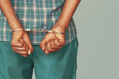 Arrested african man handcuffed hands at the back isolated on gray background. Prisoner or arrested african terrorist, close-up of hands in handcuffs. Stock Photo