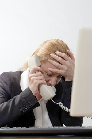 Office manager woman screams into the phone. Face of office manager in stress with a lot of phone calls at same time. Busy office worker female working and answering a lot of calls at the same time.