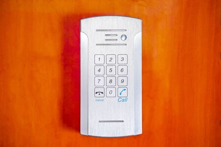 Secure password on keyboard for opening home house door on red wooden background. Password code Security keypad system protected in Public Building. The security code combination to unlock the door.