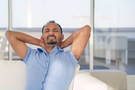 African american man has a back pain. Man suffering from neck pain at home.