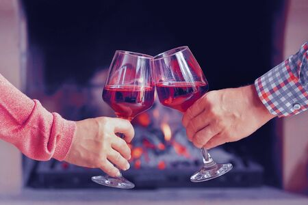 Man and woman hand toasting wine glasses in front of lit fireplace at home. Elderly couple have romantic dinner with red wine over fireplace background. Romantic winter night for couple in love. Toning.
