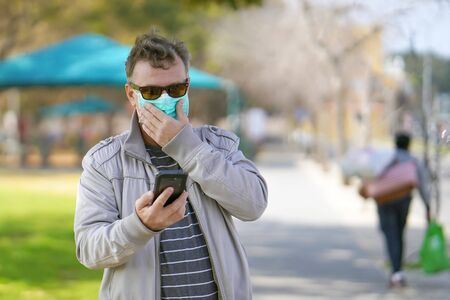 Man wearing medical mask. Male wearing medical mask in street in city and speaks on the phone. Male walking on the street wearing protective mask as protection against infectious diseases.