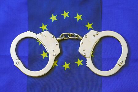 FreedomHandcuff on the flag of European Union. Flag of European Union and handcuffs, European Union law concept. Closeup, copy space for text. 免版税图像