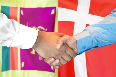 Business handshake on the background of two flags. Men handshake on the background of the Sri Lanka and Denmark flag. Support concept Archivio Fotografico
