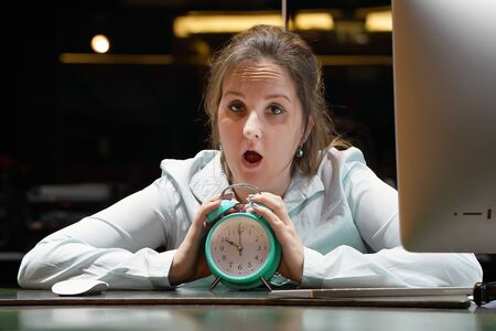 Woman holds an alarm clock in her hand in the workplace and looks at the camera. Female office worker holds an alarm clock in her hand at her desk. Woman holding a clock. Time management concept.