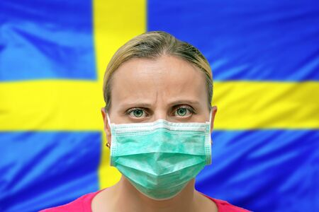 Masked woman face looking at the camera on flag Sweden background. The concept of attention to the worldwide spread of the coronavirus worldwide. Coronavirus, virus in Sweden.