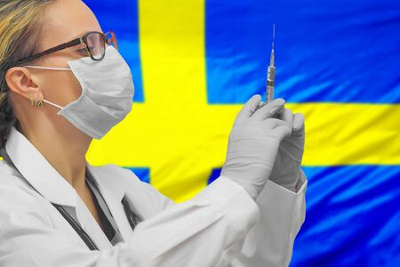 Female doctor or nurse in gloves holding syringe for vaccination against the background of the Sweden flag. Medicine concept and fight the virus. Coronavirus in Sweden.