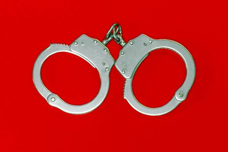 Handcuffs on a red background. The concept of crime bribes. 免版税图像
