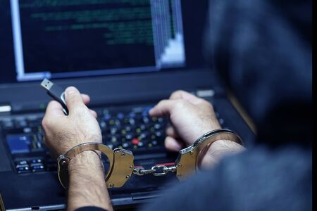Hands of a hacker in handcuffs holding USB. Prisoner or arrested terrorist in handcuffs, selective focus. Back view. 版權商用圖片